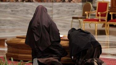 Two nuns knees over the casket of late Cardinal Bernard Law.