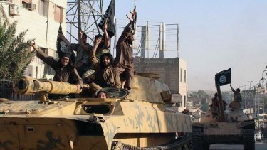 Islamic State fighters sit on a tank in Raqqa, Syria.