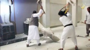 Jihadists use sledgehammers on a toppled statue in a museum at a location thought to be Mosul.