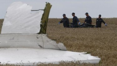 A body is removed from the crash site. Debris from the plane will contain missile fragments, experts say.