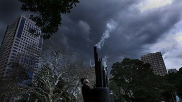 Grey skies, grey mood ... Walk Against Warming protesters in Belmore Park with a simulated wood-fired power station.