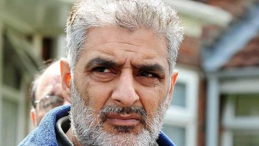 Tariq Jahan holds a picture of his son Haroon Jahan in Birmingham on Wednesday. Haroon Jahan died after being knocked down by a car along with two other men while protecting their community from looters.
