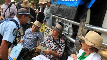 Narrabri farmer Kim Revell locks herself to a heavy vehicle trying to enter Santos' Leewood reverse-osmosis plant.