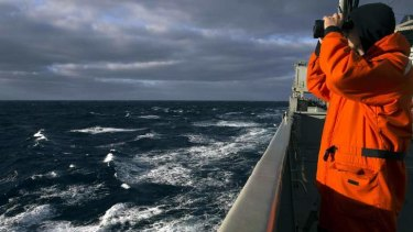 Able Seaman Marine Technician Matthew Oxley stands aboard the Australian Navy ship the HMAS Success looking for debris in the southern Indian Ocean.