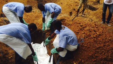 Volunteers lower a corpse, which is prepared with safe burial practices to ensure it does not pose a health risk to others and stop the chain of person-to-person transmission of Ebola, into a grave in Kailahun, Sierra Leone.
