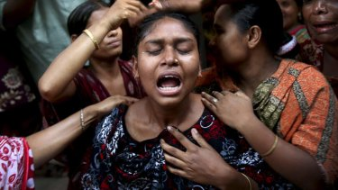 A woman is comforted by family members and others after she identified the body of her relative recovered from the rubble of the garment factory building which collapsed last week, in Savar, near Dhaka, Bangladesh.
