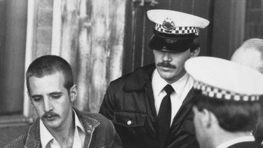 Julian Knight, left, being taken away by police after the Hoddle Street shooting.