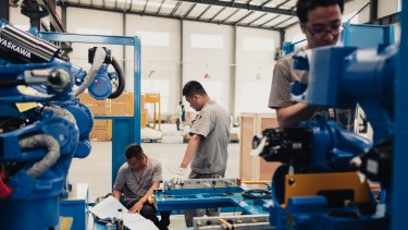 Workers assemble robots at a factory in Shenyang, China. While technology takes jobs away, it also creates complex tasks, leading to new roles.