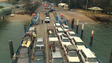 A smoke haze hangs over Dunwich at North Stradbroke Island where 900 campers are expected to evacuate via car barges.