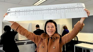 Sumin Sun holds a Senate ballot paper just over a metre long while pre-voting on August 20.