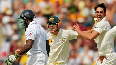 Mitchell Johnson of Australia celebrates after dismissing Michael Carberry.