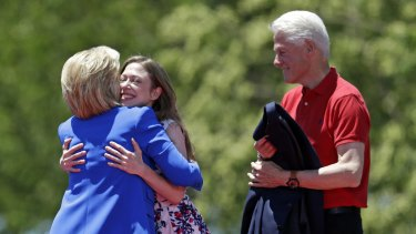 Chelsea Clinton hugs democratic presidential candidate, former Secretary of State Hillary Rodham Clinton, as former President Bill Clinton, right, watches them.