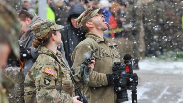 A US Army soldier plays with falling snow during the official welcoming ceremony of the US troops in Zagan, Poland this month.