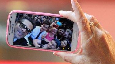 Self spree: Brad Pitt poses with fans.