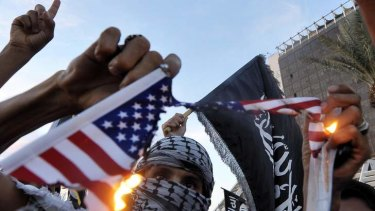 Protesters burn a replica of the US flag during a demonstration against the capture of an al-Qaeda suspect Abu Anas al-Liby.