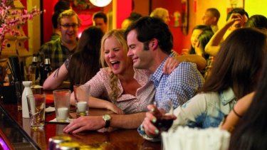 Amy Schumer as a lustful barfly and Bill Hader as a surgeon and potential love interest, in <i>Trainwreck</i>.