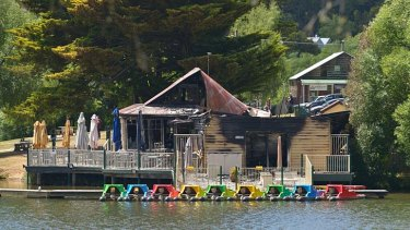 Police and fire investigators analyse the scene of the Boathouse Cafe fire.