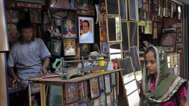 A Sri Lankan Muslim woman walks past a picture framing shop where a portrait of President Maithripala Sirisena is on display.
