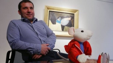 Chance find: Hungarian art historian Gergely Barki with a plush figure of Stuart Little in front of the painting by Hungarian artist Robert Bereny, <i>Sleeping Lady with Black Vase</i>.