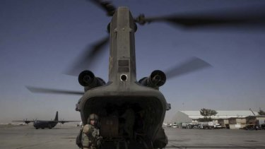 An air crewman from an Australian Army chinook, based at Kandahar Airfield, organises the pick-up of a load during a resupply mission to a forward operating base in Afghanistan.