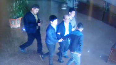 Chinese social media has been widely sharing a picture of a man resembling Mr Guo being led through an airport by what appear to be plain-clothes police.