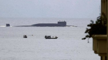 Fishermen look at a Chinese nuclear submarine that sails past Yalong Bay in Sanya, south China's Hainan Province.