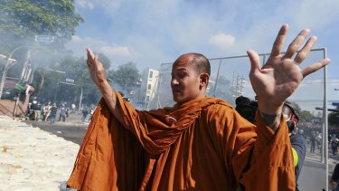 A Buddhist monk raises his hands in a bid to stop policemen firing tear gas in Bangkok on Sunday.