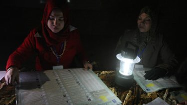 Undeterred by darkness and danger ... Iraqi election officials count votes using a rechargeable battery lamp at a polling station in Sadr City.