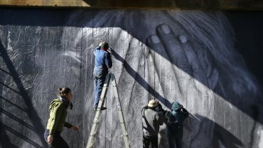 Artists paste up a mural of indigenous elder Uncle Larry Walsh.