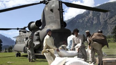 Food aid ... Pakistanis with flour from a US helicopter.