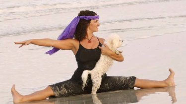 Doga instructor Suzi Teitelman and dog Roxy  in a straddle pose at Ponte Vedra Beach, Florida.
