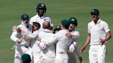Australia's captain Steve Smith, left, and David Warner, second left, celebrate after winning the first Test against India in Pune.