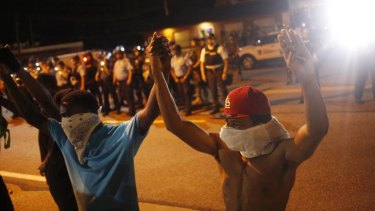 Protestors wearing masks raise their hands above their heads as they stand in front of police officers monitoring nighttime demonstrations in Ferguson.