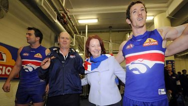 Julia Gillard joins (from left) Brian Lake, coach Rodney Eade and Robert Murphy in singing the song after the win over North Melbourne on August 1, 2010.