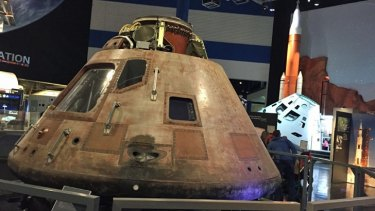 The actual Apollo 11 Command Module, battered  from reentry, with Orion and its SLS rocket behind.
