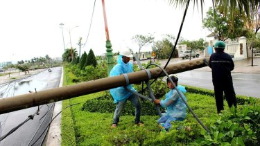 Workers repair a fallen electricity pole in the central province of Phu Yen, Vietnam.