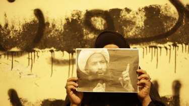 An anti-government protester in Bahrain holds a picture of Sheikh Nimr during clashes between police and protesters in Sanabis.