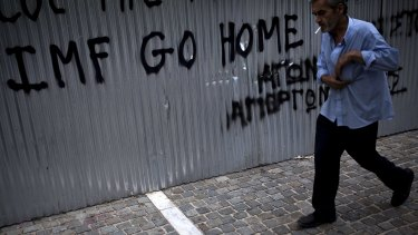 A man walks in front of a graffiti reading 'IMF go home' in Athens on Saturday.