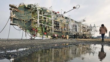 Trail of devastation . . . a fishing boat washed away by the tsunami lies on its side at Hachinohe in northern Japan.