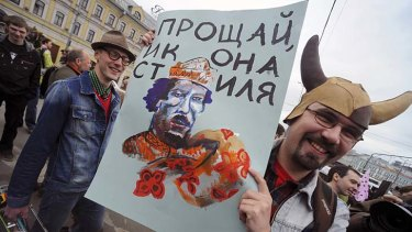 """A participant stages a performance as he attends a May Day rally on International Workers' Day in Moscow. The placard reads, """"farewell icon of style""""."""