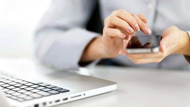 Unwind. 20 August 2013. Businesswoman using smart phone. iStock Photo File #23229746
