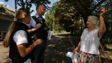 Deputy head of the OSCE mission Alexander Hug (second from right) talks with retired kindergarten teacher Era Pavlovna, 76, (right) after handing her a pamphlet on how to return debris of MH17 crash, in Rassypnoe.