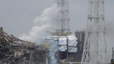 The damaged No. 4 unit of the Fukushima Daiichi nuclear complex. White smoke is billowing from the No. 3 unit.