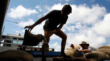 Preparing for higher floodwaters ... volunteers stack sandbags in Rockhampton yesterday.