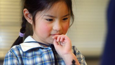 Prep student Julia Goh ponders a game of chess at Doncaster Primary School, playing it in her lunch break.