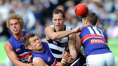 Surrounded by three Dogs ... Geelong's James Kelly handballs out of pressure during the Cats' commanding win yesterday.