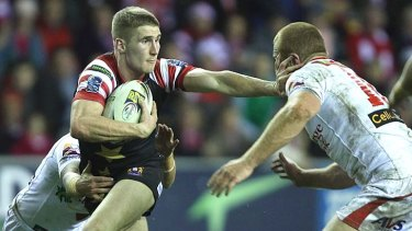 Sam Tomkins of Wigan Warriors is tackled by Nathan Fien and Jon Green.