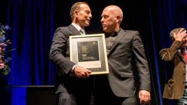 'I'll leave litterateurs to make their comments on politics': Tony Abbott hands Richard Flanagan the Prime Minister's Literary Award for fiction.