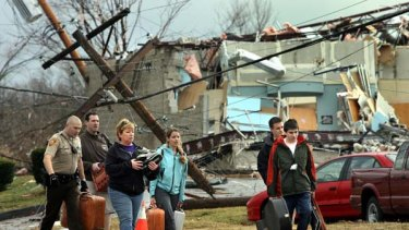 Blown apart ... a police officer helps evacuate residents from their wrecked home in Missouri. Tornadoes have killed six people.