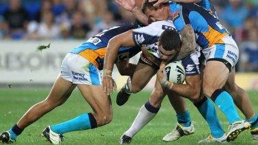 Greg Inglis tries to crash his way through the Gold Coast defence.